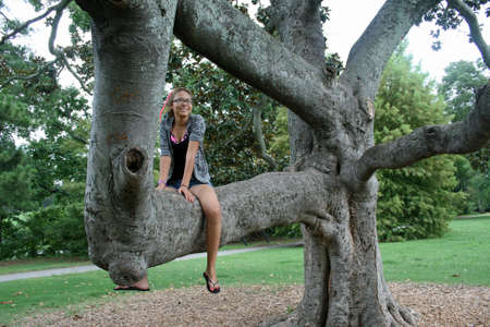 Girl sitting on gnarled Southern Magnolia tree