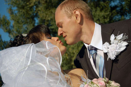 Portrait of the a newly wedded couple kissing Imagens