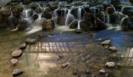 Waterfall at night with curve placed stones Stock Photo