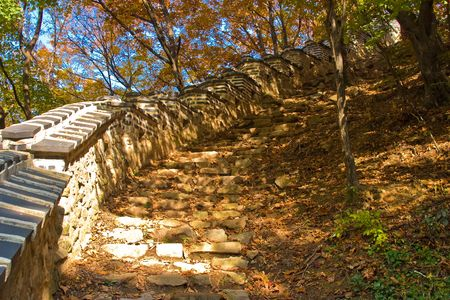 Asian ancient wall and step stones at fall forest