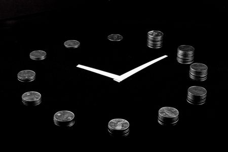 A clock on black background made from silver coin towers showing concept of loosing money as time goes