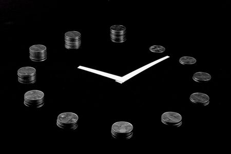 A clock on black background made from silver coin towers showing concept of earning money as time goes Stock Photo