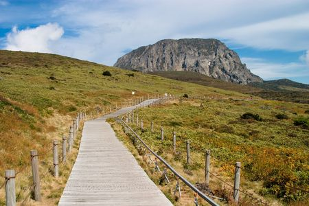 Mountain view over a plato with orange grass and wooden walk path Stock Photo