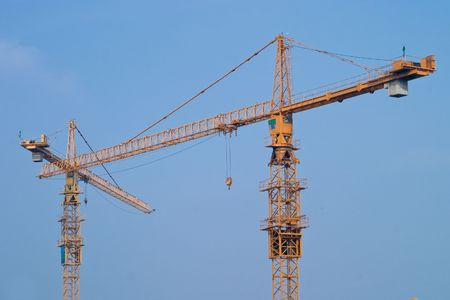 Two crossed yellow cranes over blue sky on a construction site