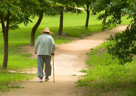 guy with walking stick: Active male senior with big hat and stick walks on park road Stock Photo