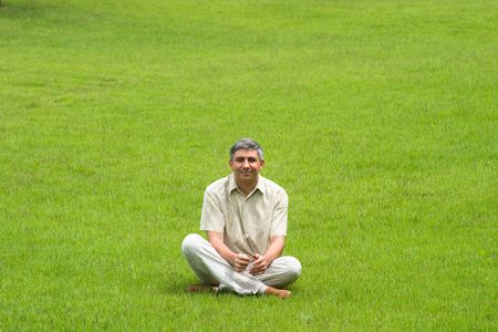 Smiling man sitting on grass field Stock Photo