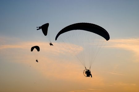 Paramotor gliders over sunset sky