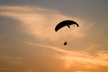 Paramotor glider over sunset sky Stock Photo