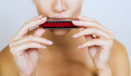 A beautiful young woman is playing harmonica, close-up  photo
