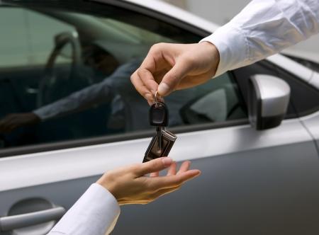 woman receiving car key from man photo