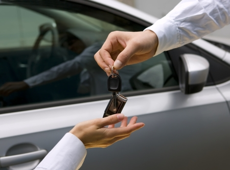 car dealer: woman receiving car key from man
