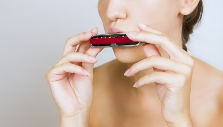 harmonica: A beautiful young woman is playing harmonica, close-up  Stock Photo