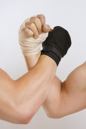 Hand in a white glove and hand in a black glove clasped arm wrestling, good and evil opposition