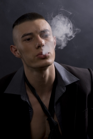 man in a suit with a cigarette on a black background photo
