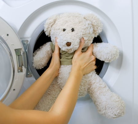 woman loading fluffy toy in the washing machine Фото со стока