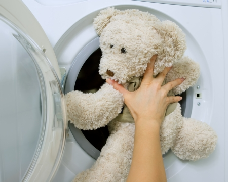 launderette: woman loading fluffy toy in the washing machine Stock Photo