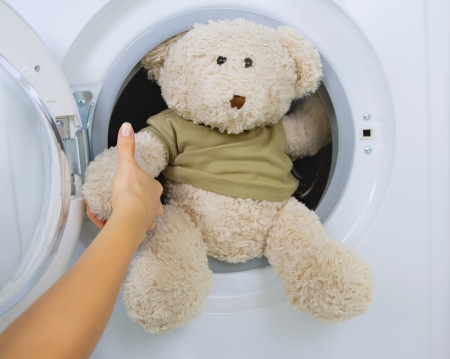 lave: woman taking fluffy toy from washing machine