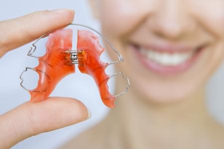 Smiling girl holding braces for teeth