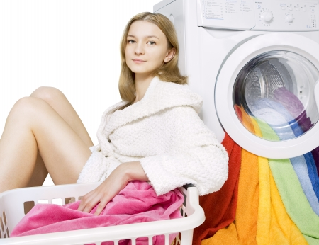 young girl and washing machine with colorful things to wash, isolated Stock Photo - 20620340