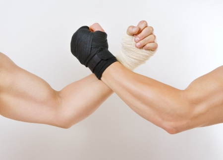 will power: Hand in a white glove and hand in a black glove clasped arm wrestling, good and evil opposition