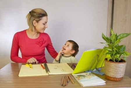Happy woman helping small kid write photo