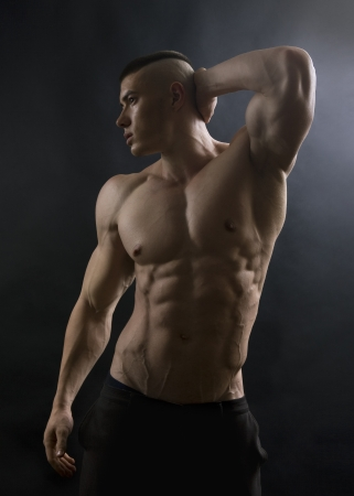 Young sexy man with athletic body posing on black background. Stockfoto