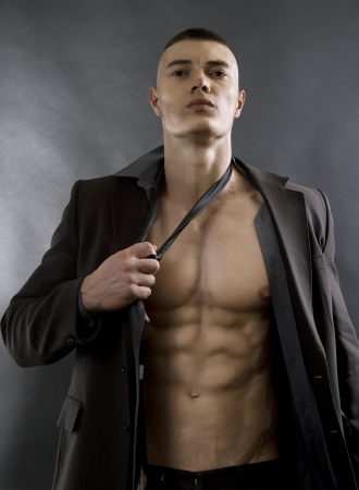 Young sexy man with athletic body posing on black background. photo