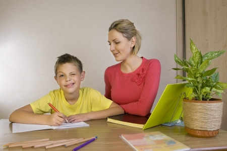 Woman helping her son with homework photo