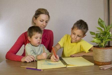 Happy mother helping her sons with homework photo