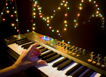 chill out: Musician playing on musical keyboard  Close up of a hand playing a MIDI controller keyboard in black background
