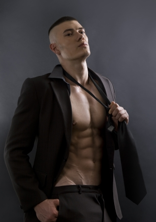 Young sexy man with athletic body posing on black background. Stock Photo