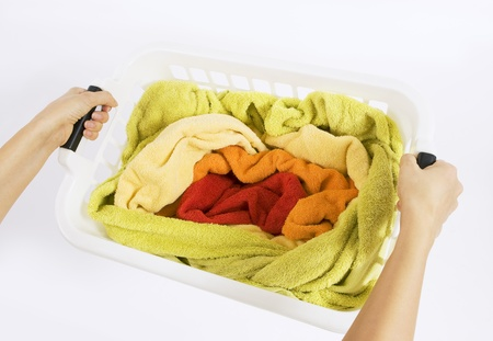 woman holding a white plastic basket with colorful laundry to wash photo
