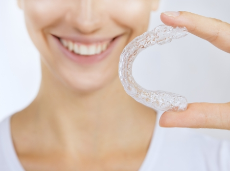 correction: smiling girl with tooth tray - Beautiful smiling girl with tooth tray (hands holding individual tooth tray) Stock Photo