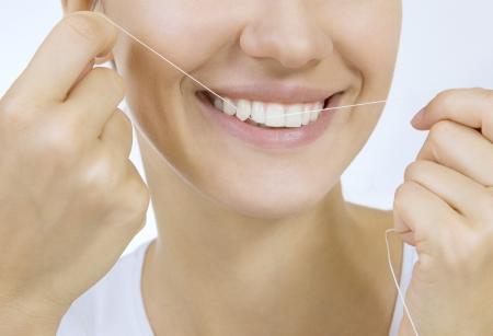 Femme et dents soie - Jeune femme caucasienne soie dentaire ses dents (close up femme sourire) Banque d'images - 21510927