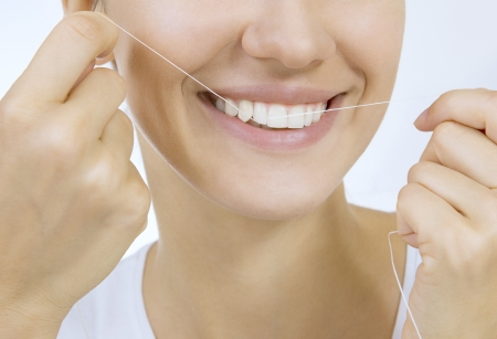 Woman and teeth floss - Young caucasian woman flossing her teeth (close up woman smile)