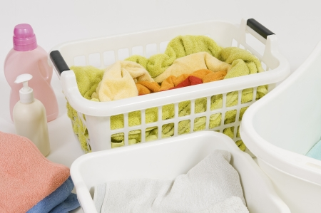 Wash colored laundry. Detergents and towels in white plastic basket, basket with colorful laundry to wash (handwash)