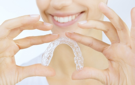teeth whitening: Beautiful smiling girl with tooth tray (hands holding individual tooth tray) Stock Photo