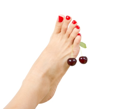female foot with red pedicure and cherry close up, isolated photo