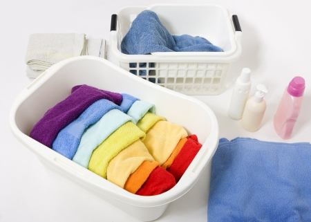 lave: Wash colored laundry. Detergents and towels in white plastic basket, basket with colorful rainbow laundry to wash