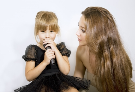 Pretty little girl singing in microphone, mother and little girl with a microphone photo