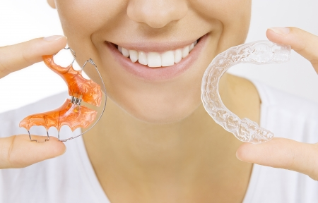 trays: Beautiful smiling girl holding retainer for teeth  dental braces  and individual tooth tray