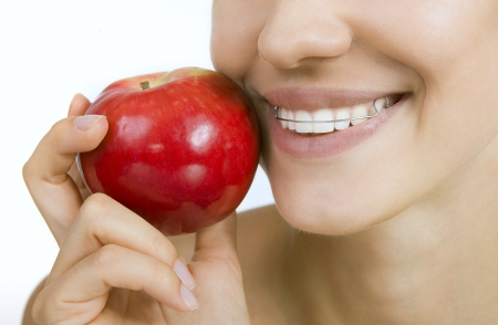 crooked: Beautiful smiling girl with retainer for teeth - healthy teeth and apple Stock Photo
