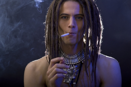 dreadlock: a young stylish man with dreadlocks and a lot of silver jewelry smoking a cigarette, blue filter effect
