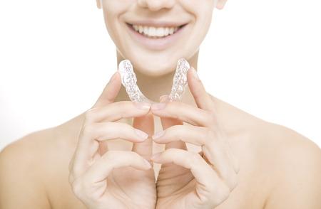 bandejas: Hermosa ni�a sonriente con la bandeja del diente (manos que sostiene la bandeja dental individual)
