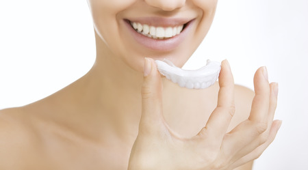 Beautiful smiling girl with tooth tray (hands holding individual tooth tray) Stockfoto