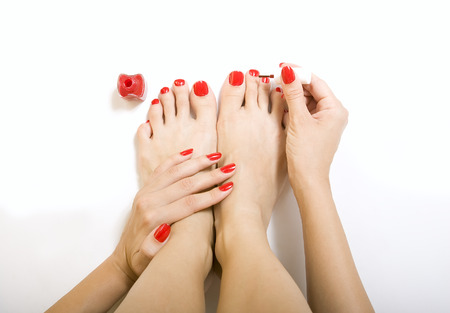 pedicure process - red manicure and pedicure, female foot with red pedicure