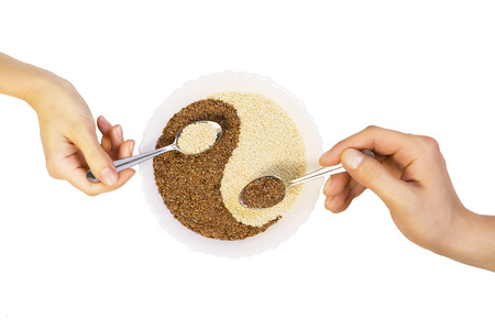 duality: Eastern cuisine - man and woman hold spoons with sesame seeds in yin yang shape near plate, isolated