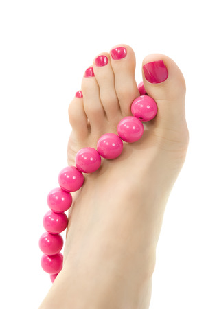 female foot with pink pedicure and accessory close up photo