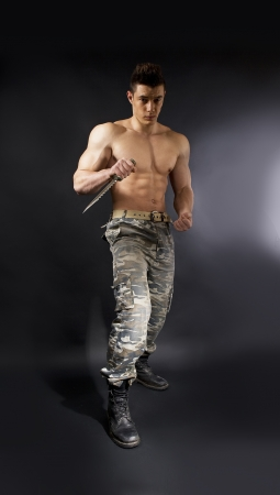 army boots: attractive soldier with athletic body with knife over dark background