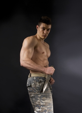 attractive soldier with athletic body with knife over dark background photo